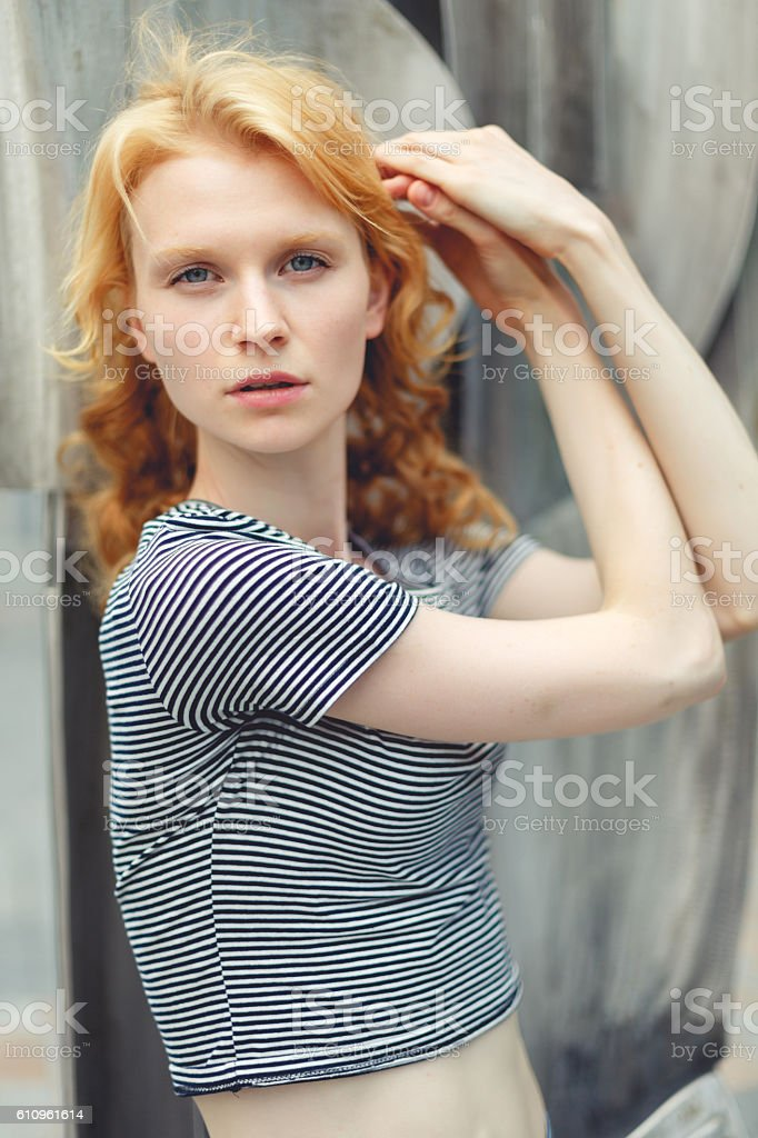 Ginger girl with curly hair standing at construction, photo toned stock photo