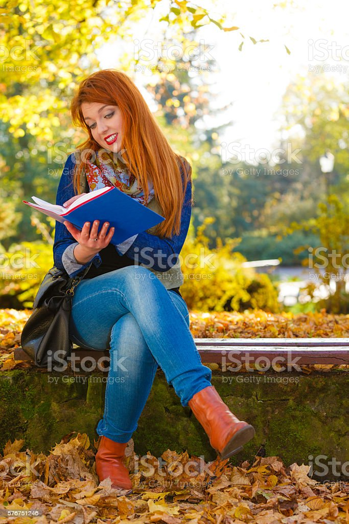 Ginger hair girl is reading book in park. stock photo