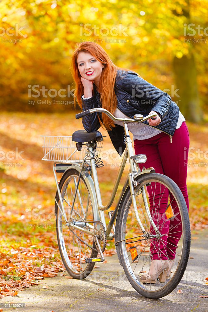 Ginger hair girl with her bike in the park. stock photo