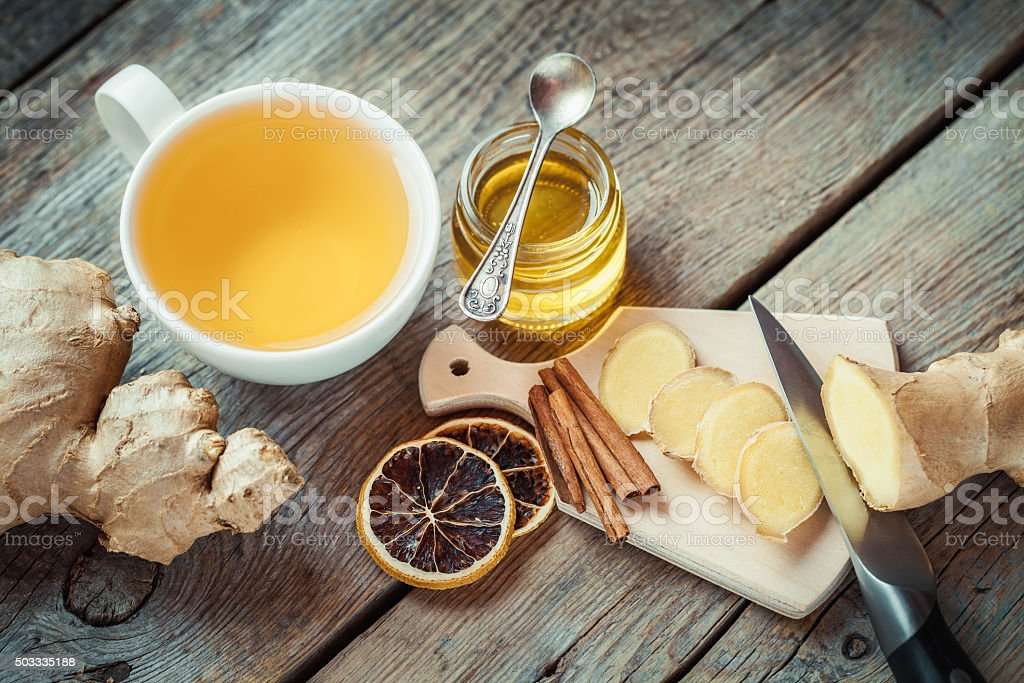 Ginger, jar of honey, tea cup on kitchen table. stock photo