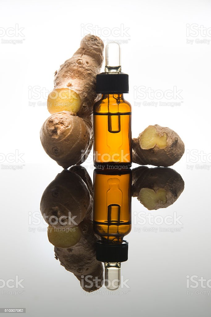 Ginger root with essential oil bottle, in amber bottle and dropper. stock photo