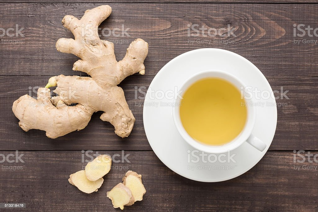 Ginger tea and ginger on the wooden background. stock photo