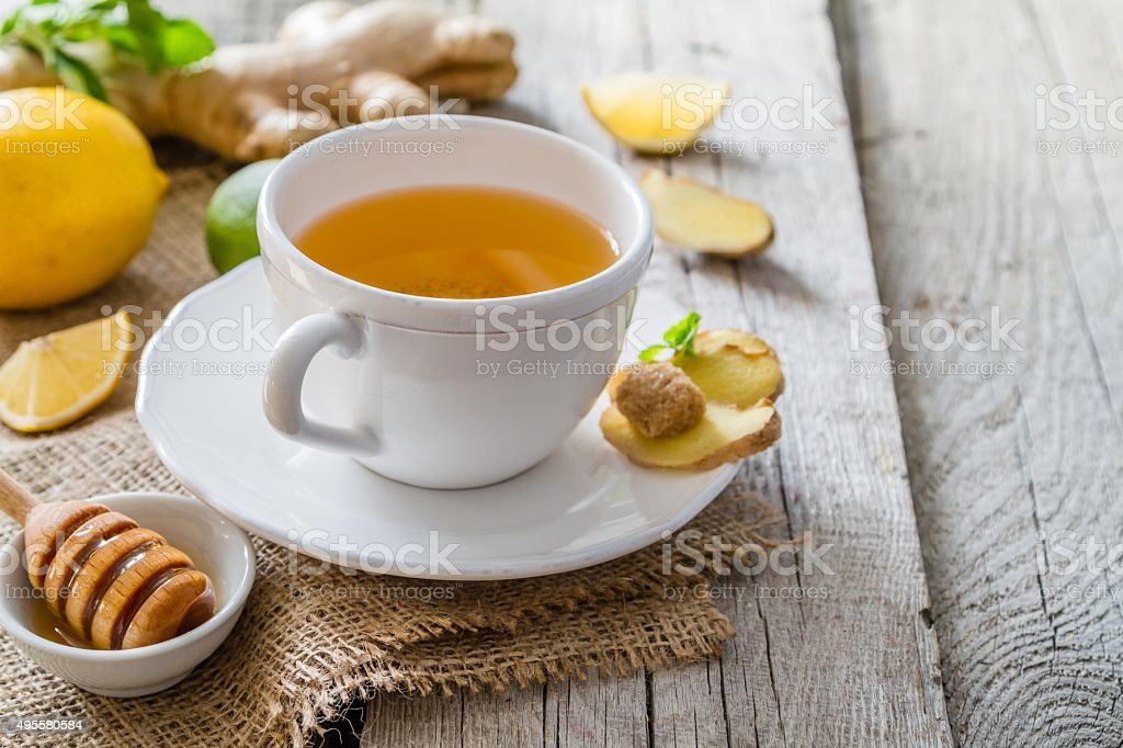 Ginger tea and ingredients on rustic wood background stock photo