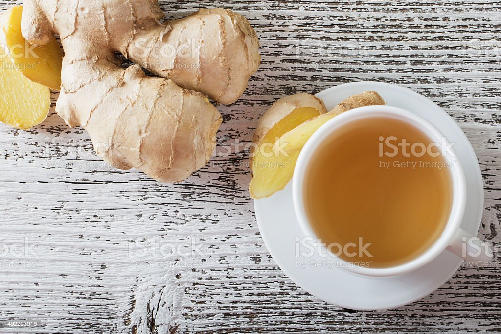 Ginger tea in a white cup on wooden background stock photo