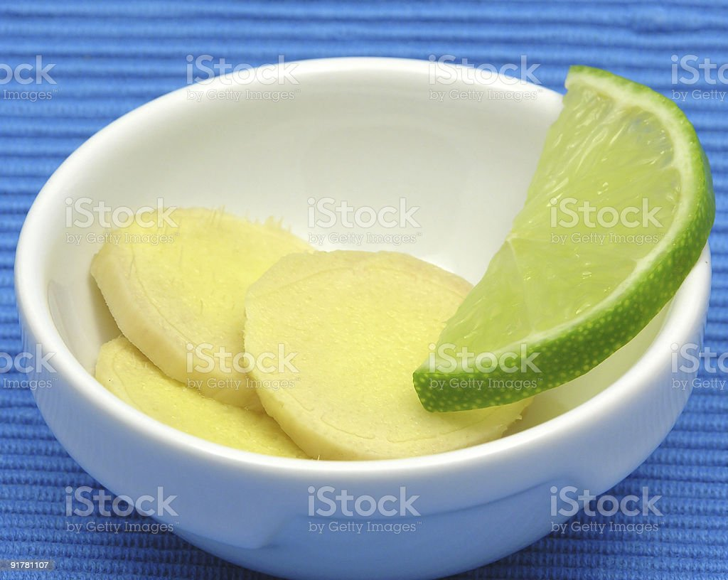 Ginger with lemon in  bowl of chinaware on blue royalty-free stock photo