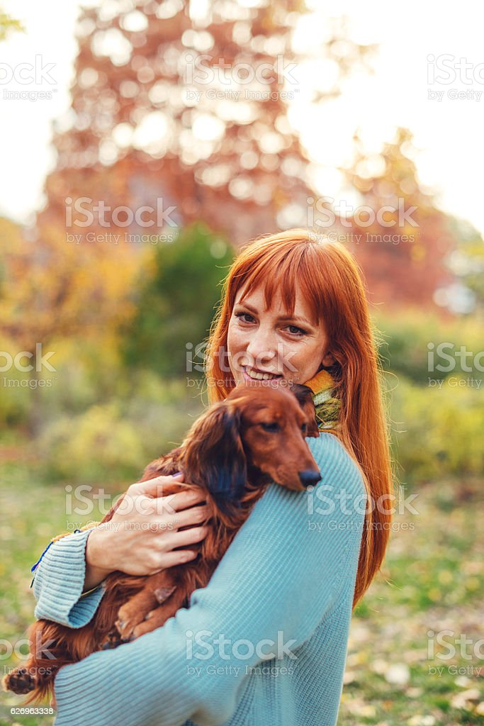 Ginger woman petting her brown dachshund dog in park stock photo