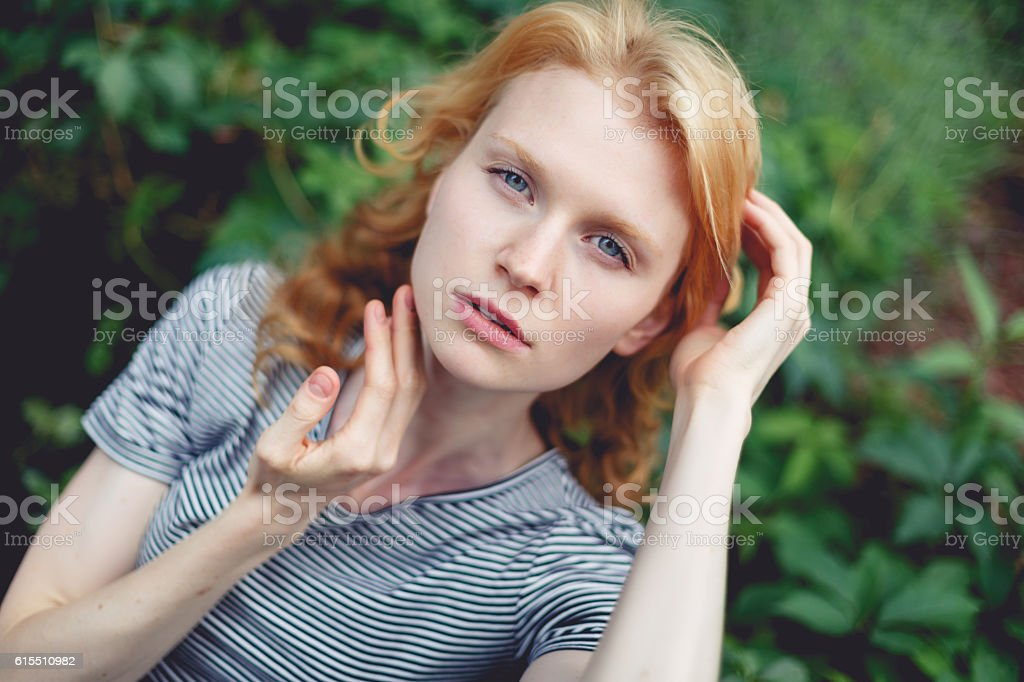 Ginger woman with curly hair in short top, tinted photo stock photo