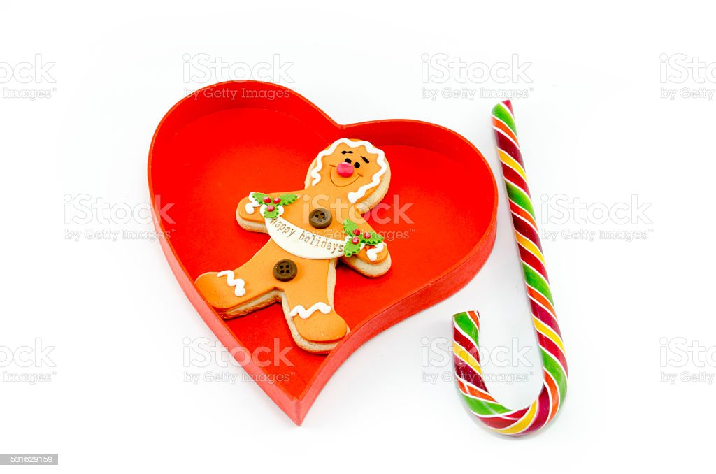 Gingerbread and a candy cane in a heart shaped box royalty-free stock photo