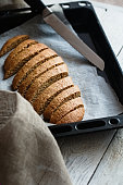 Gingerbread biscotti on a baking tray with knife