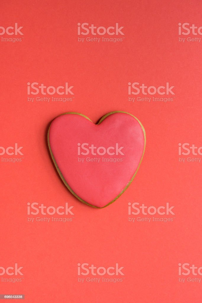 Gingerbread cookie with red icing on the top isolated on red stock photo