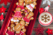 Gingerbread cookies family and cappucion on wooden table