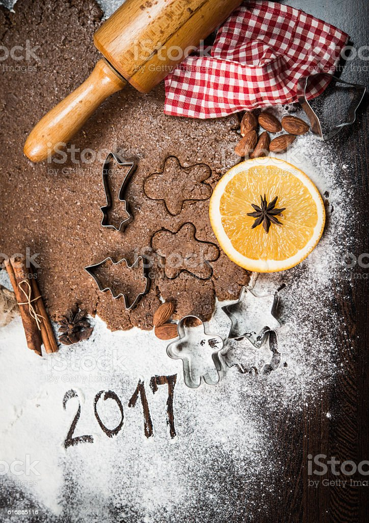 Gingerbread dough and cookie cutters with orange and spices stock photo