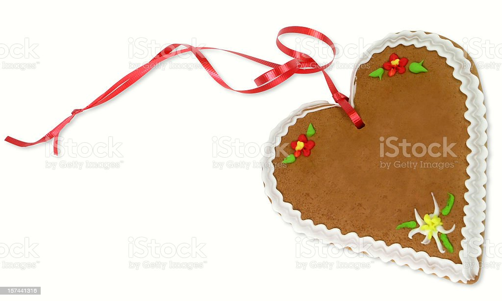 A gingerbread heart with red ribbon attached stock photo