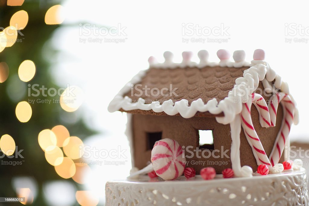 Gingerbread house in front of Christmas tree royalty-free stock photo