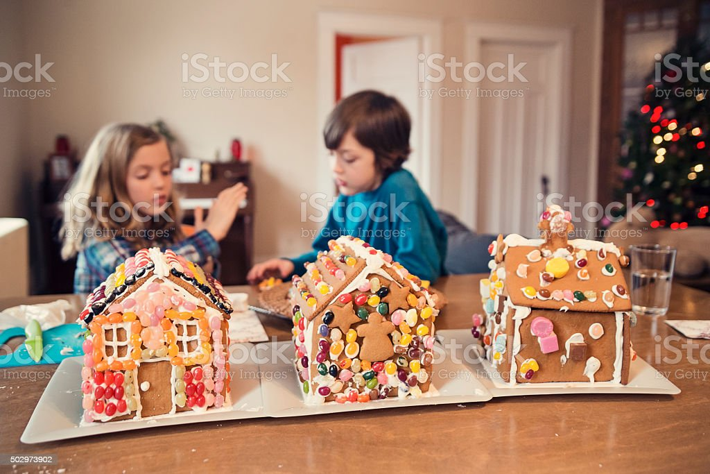 Gingerbread houses decorated with candy on messy table. stock photo