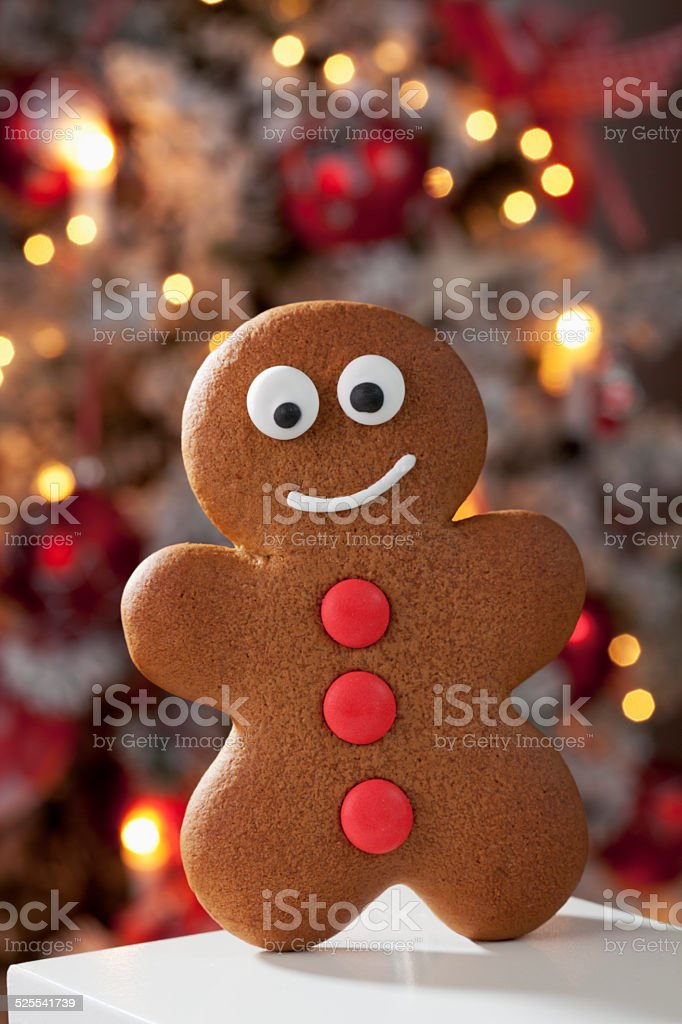 Gingerbread man close up christmas tree in background stock photo