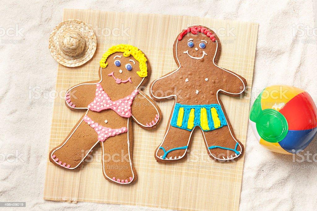 Gingerbread Man Cookie Couple Sunbathing on Beach Mat Horizontal royalty-free stock photo
