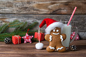 Gingerbread man in Santa hat and glass of milk