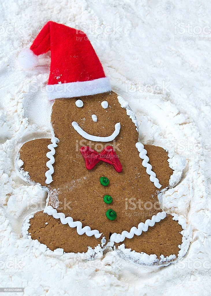 gingerbread man making snow angel stock photo