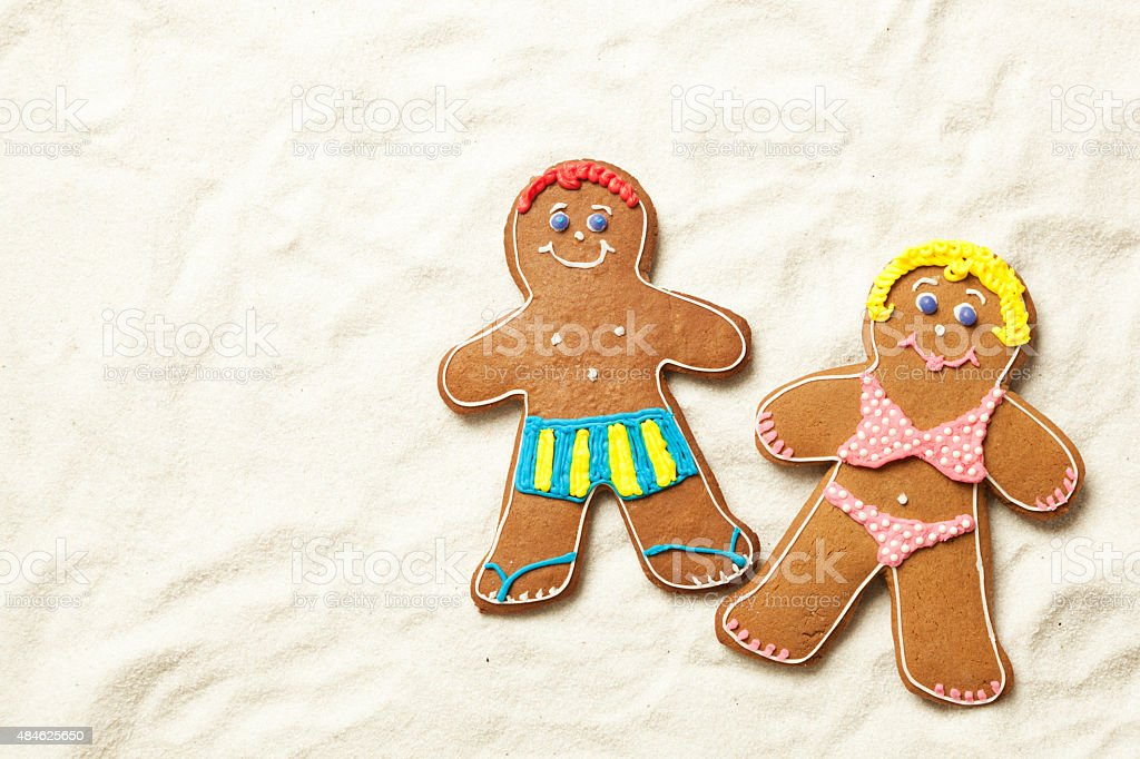 Gingerbread Man, Woman Cookie Couple in Swimsuits on Sandy Beach stock photo