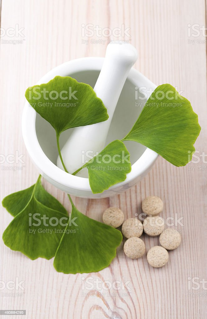 Ginkgo biloba leaves in mortar and pills stock photo