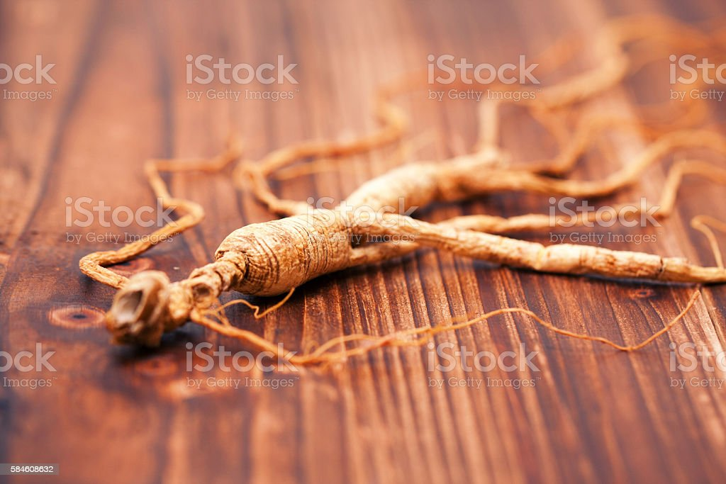 Ginseng on the wood background stock photo
