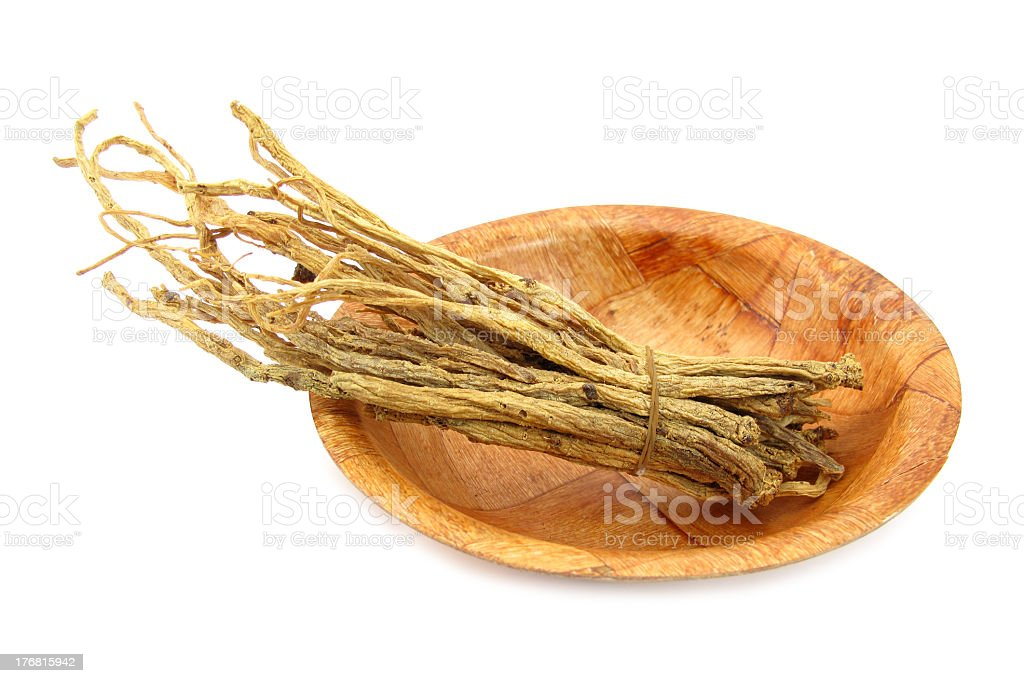 Ginseng root on a wooden plate royalty-free stock photo