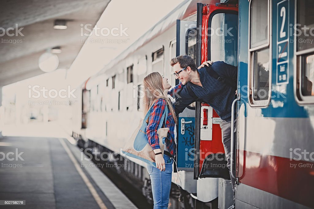girfriend  clings to a boyfriend  as he  prepares to leave stock photo