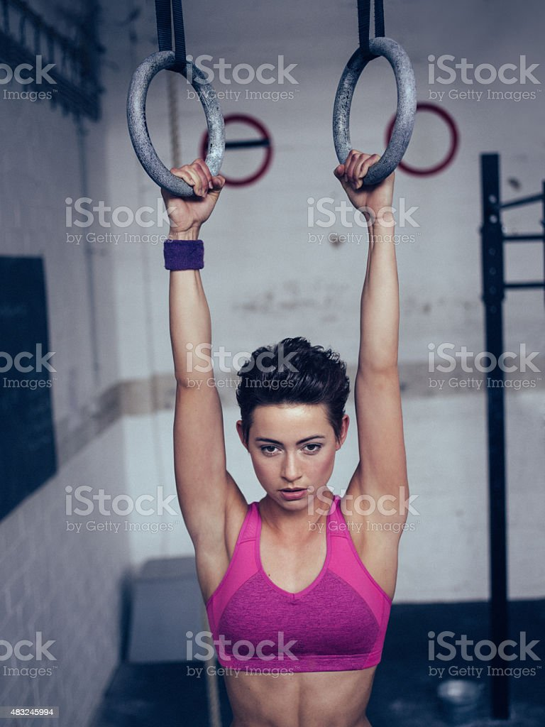 Girl about to do a pull-up on gymnastic rings stock photo