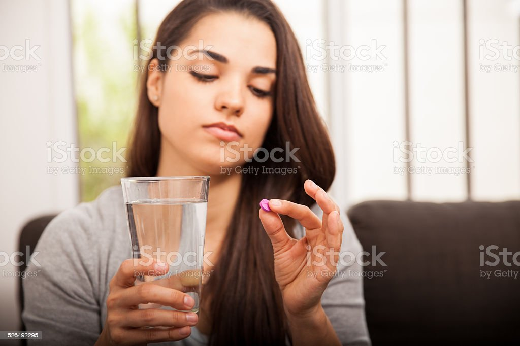 Girl about to take a pill stock photo