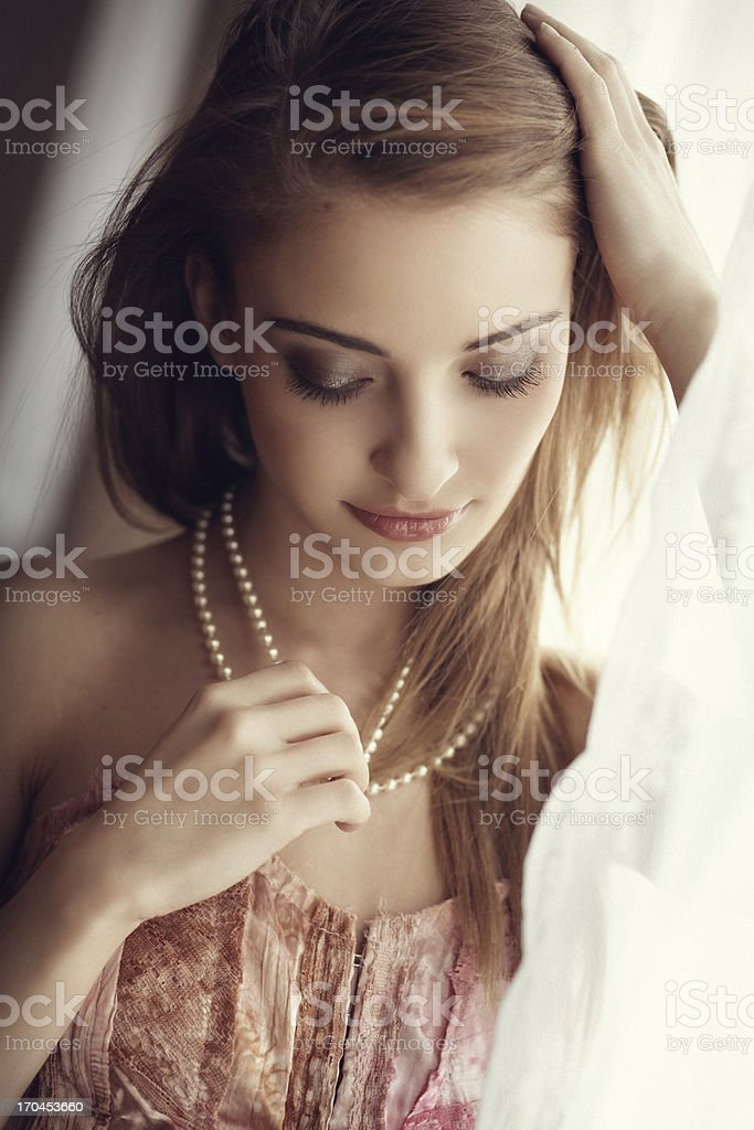 Girl adjusting her hair by the window stock photo