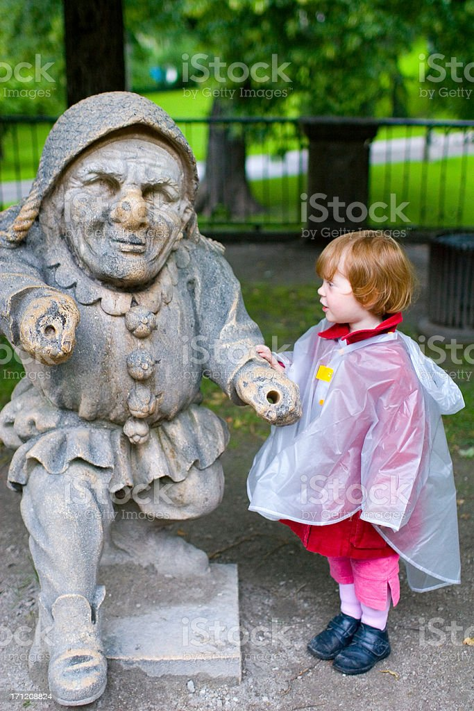 girl admiring dwarf statue royalty-free stock photo