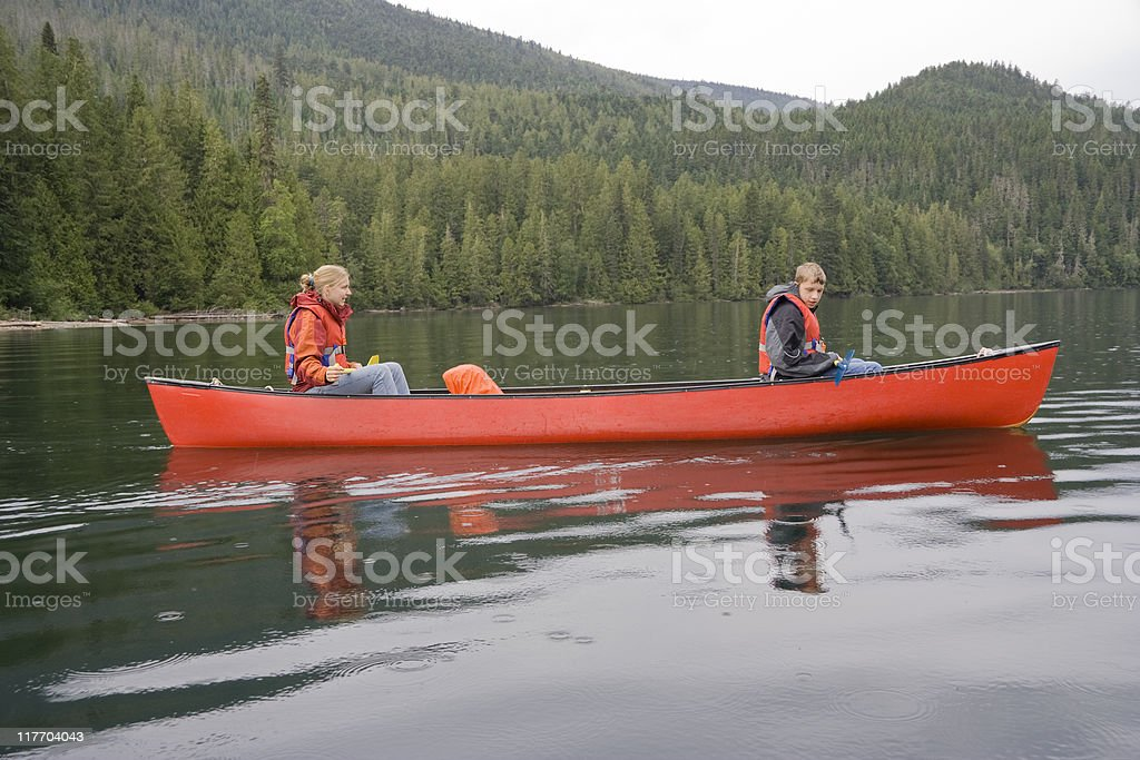 Girl and boy canoeing royalty-free stock photo