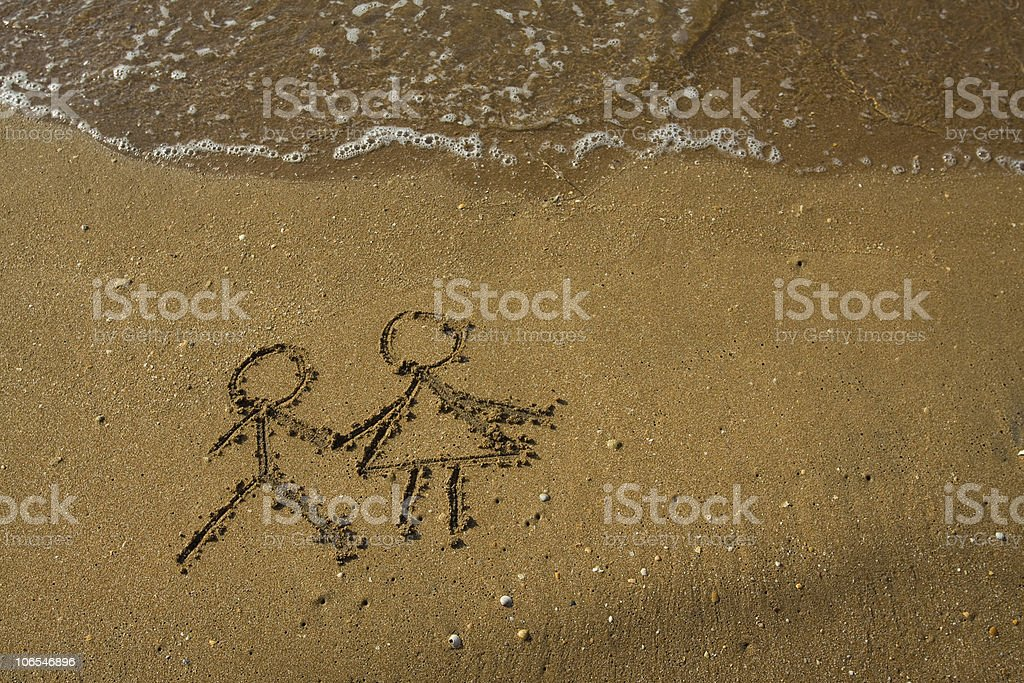 Girl and boy drawn on a beach sand. stock photo
