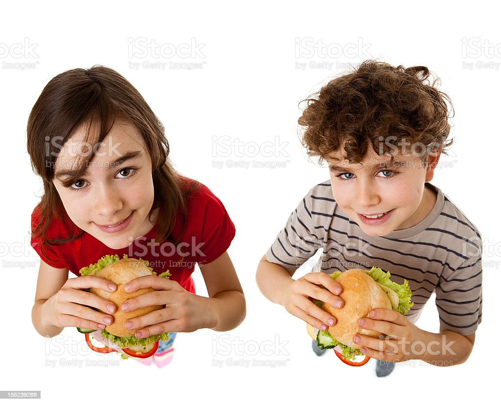 Girl and boy eating sandwiches royalty-free stock photo
