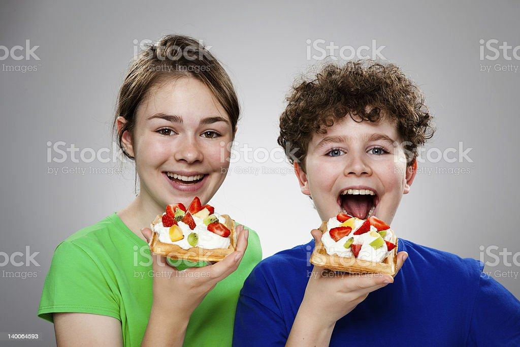 Girl and boy eating waffle with cream, fruits royalty-free stock photo