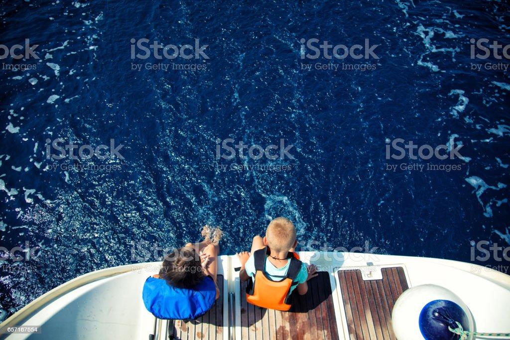 Girl and boy enjoying vacation on sailboat stock photo