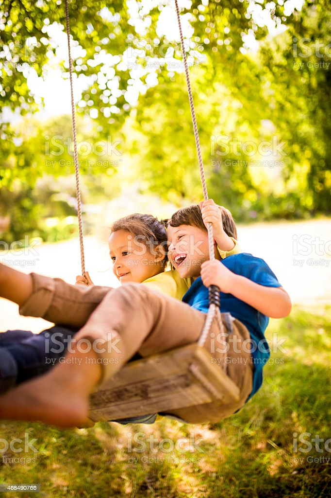 Girl and boy having fun as team to swing high stock photo