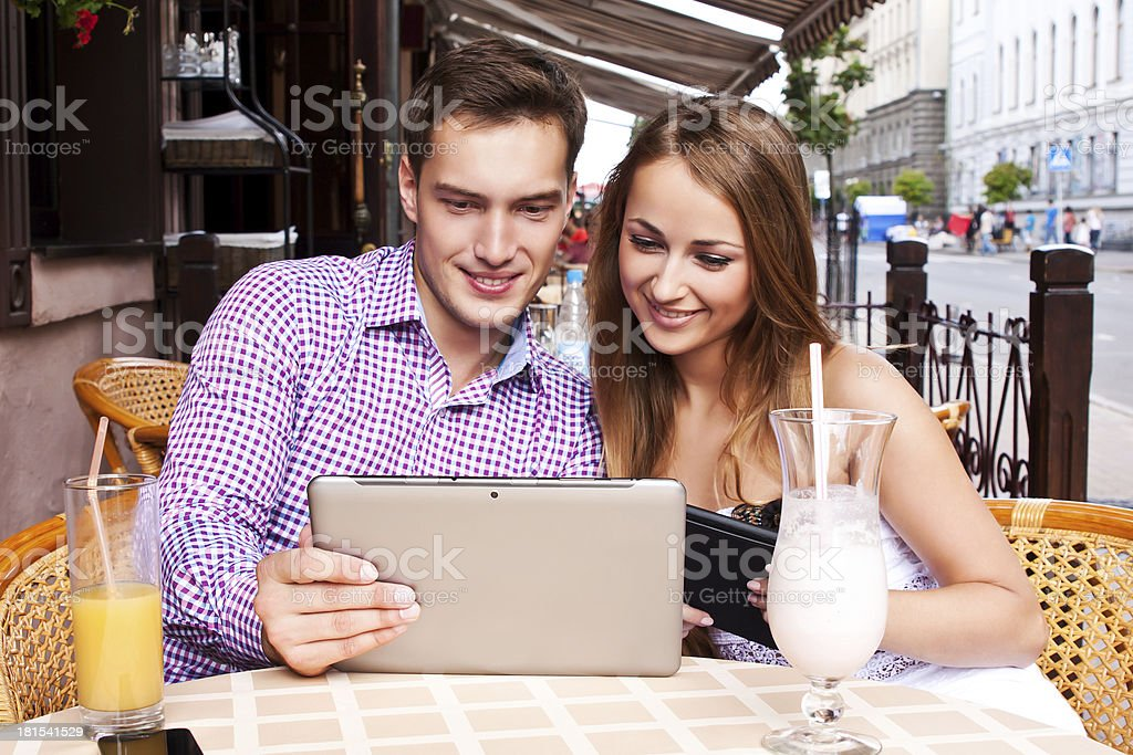 Girl and boy in cafe used  tablet computer royalty-free stock photo