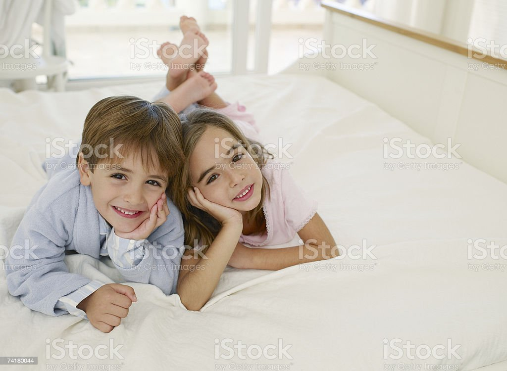 Girl and boy in robe on bed royalty-free stock photo