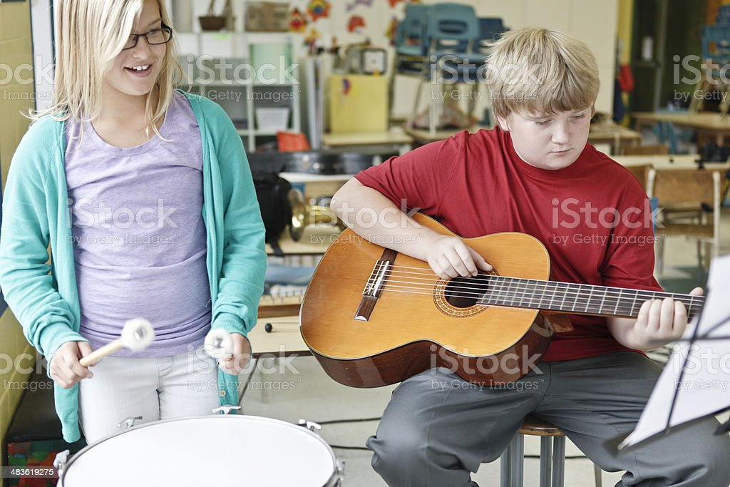 Girl and Boy Learning to Play Instruments stock photo