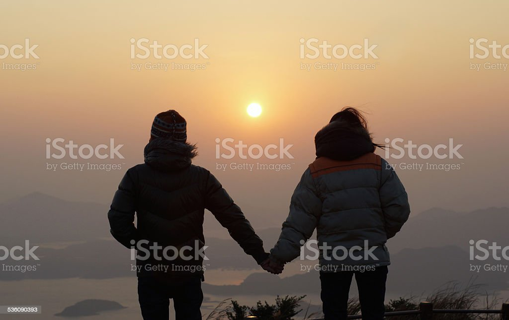 girl and boy on peak view the sun stock photo