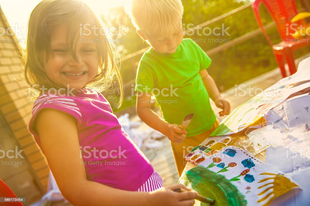 Girl and boy paint outdoors stock photo
