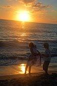 Girl and boy play at the sundown on the beach