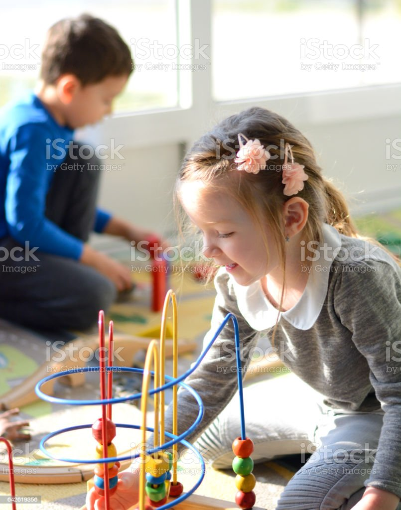 Girl and boy playing in the playroom. stock photo