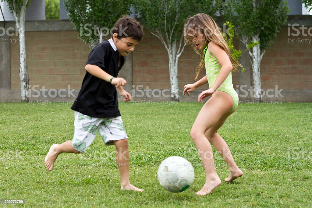Girl and boy playing soccer stock photo