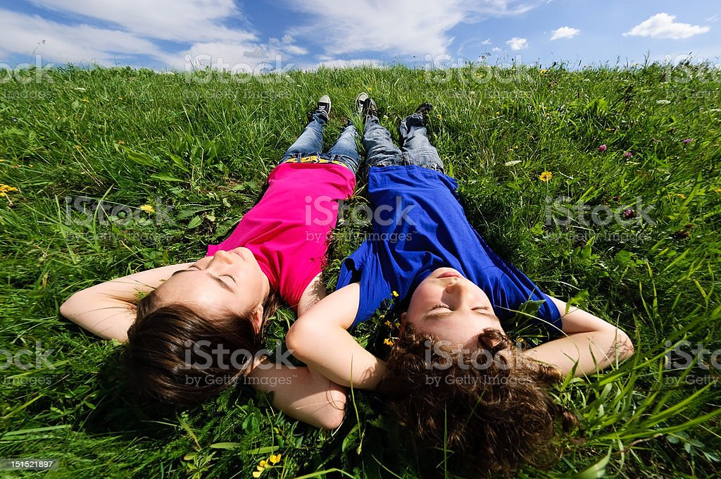 Girl and boy relaxing on green meadow royalty-free stock photo