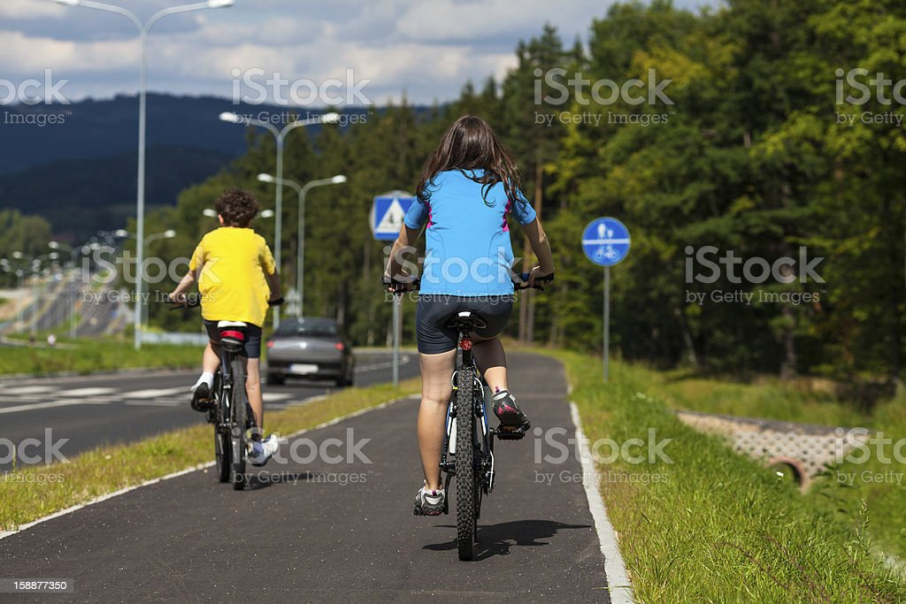 Girl and boy riding bikes royalty-free stock photo