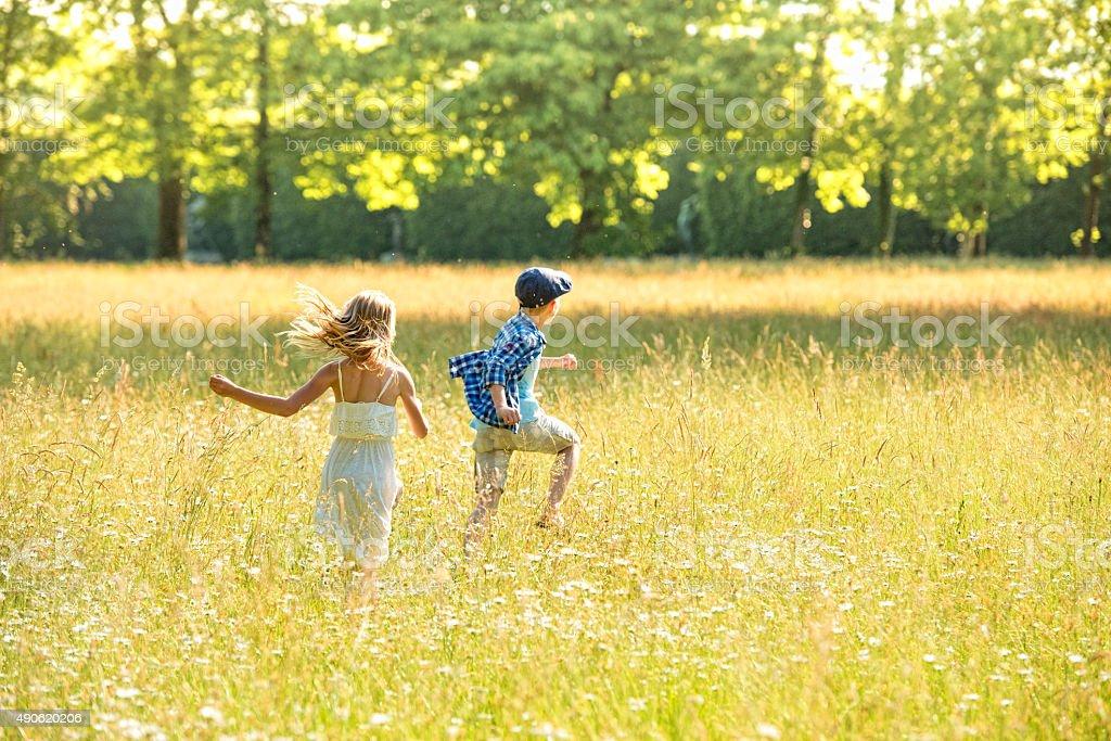 Girl and boy running across a golden meadow stock photo