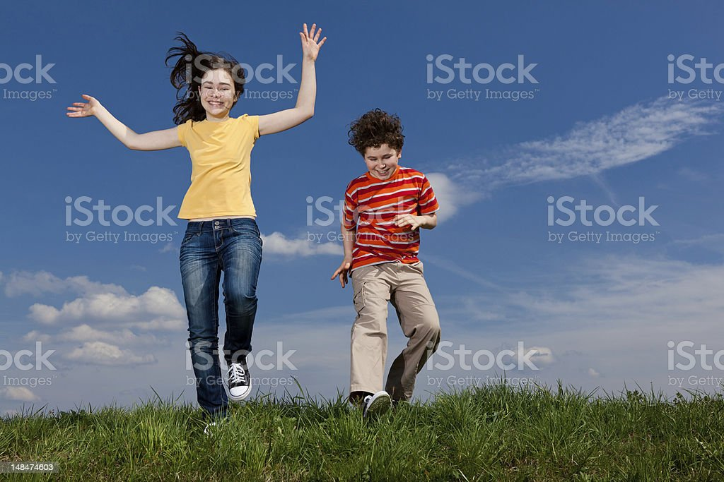 Girl and boy running outdoor stock photo
